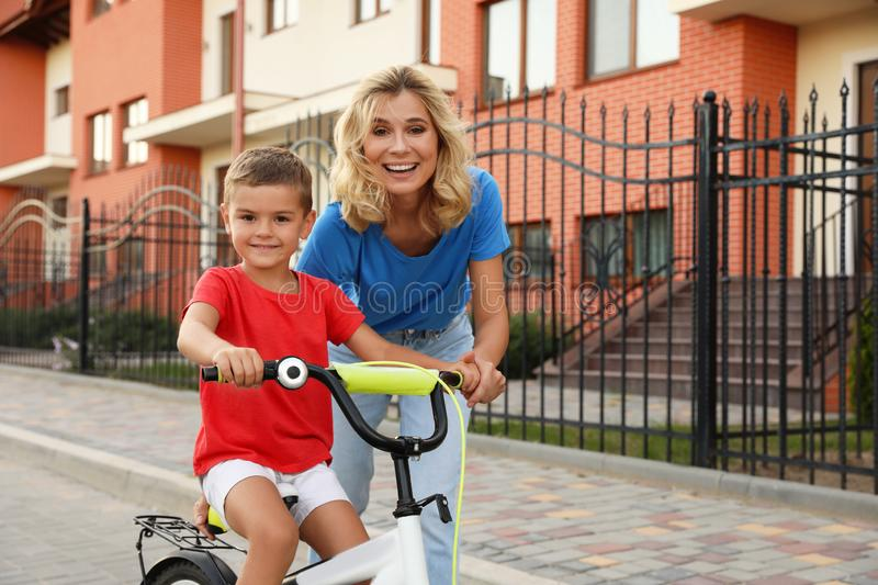 Happy mother teaching her son to ride bicycle. In city royalty free stock photo
