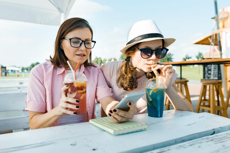 Happy mother and teen daughter talking and smiling. Parents with a kid in a summer outdoor cafe enjoying cold drinks on a hot royalty free stock images