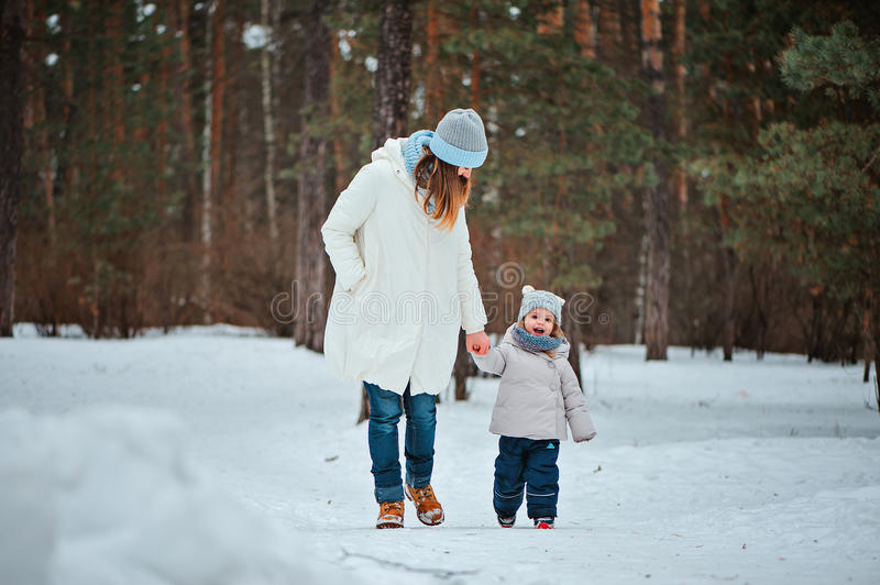 Happy mother and toddler daughter walking in winter snowy forest. Happy mother and smiling toddler daughter walking in winter snowy forest stock photography