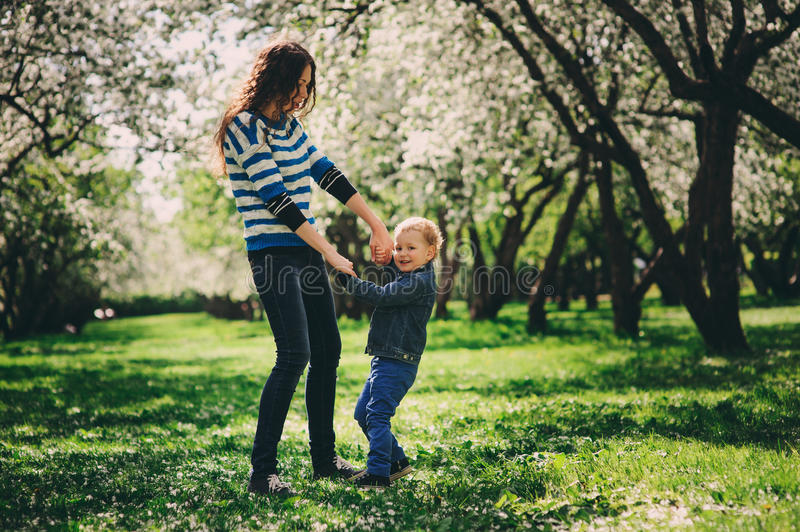 Happy mother and toddler son playing outdoor in spring or summer park stock photo