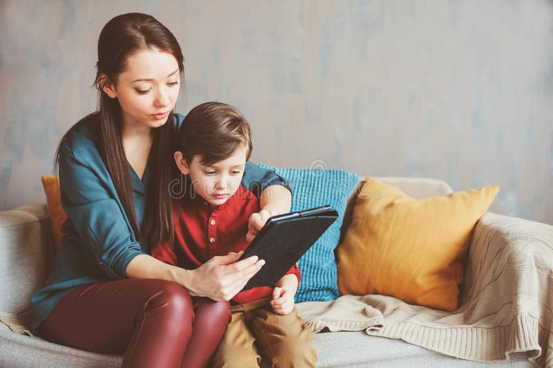 Happy mother and toddler son using tablet at home. Family playing computer or searching internet, electronic devices and kids in modern life stock images