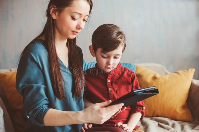 Happy mother and toddler son using tablet at home. Family playing computer or searching internet, electronic devices and kids in modern life royalty free stock photo
