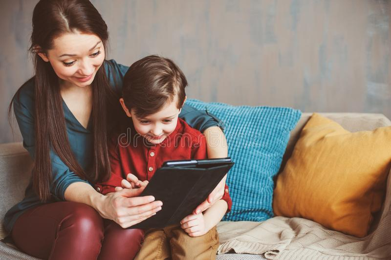 happy mother and toddler son using tablet at home. Family playing computer or searching internet royalty free stock image