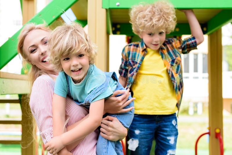 happy mother with two adorable playful little boys at playground royalty free stock photo
