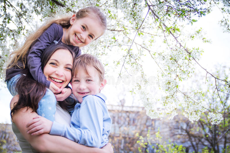 Happy mother and two children hugging in spring royalty free stock image