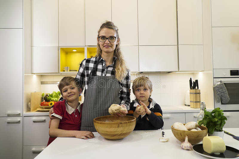 Happy mother and two kids preparing dough royalty free stock photos