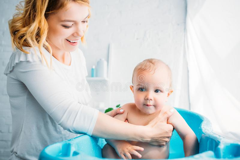 Happy mother washing her little child. In plastic baby bathtub at home stock photography