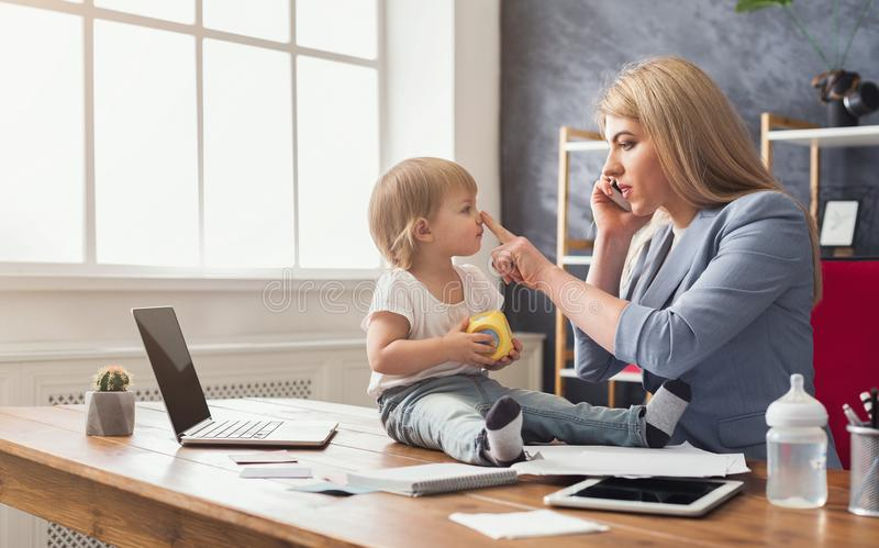 Young mother talking on phone and spending time with baby royalty free stock image