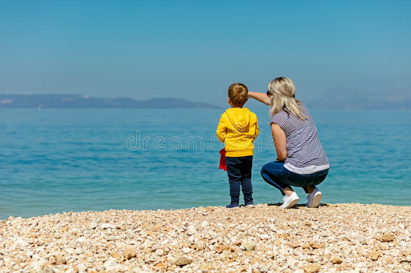 A happy mother and young child boy son having fun on a sunny beach.  royalty free stock photo