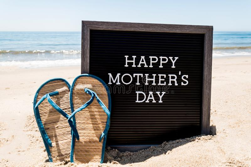 Happy Mothers day beach background with black board and flip flops stock image