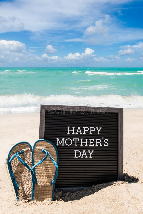 Happy Mothers day beach background with black board and flip flops stock photography