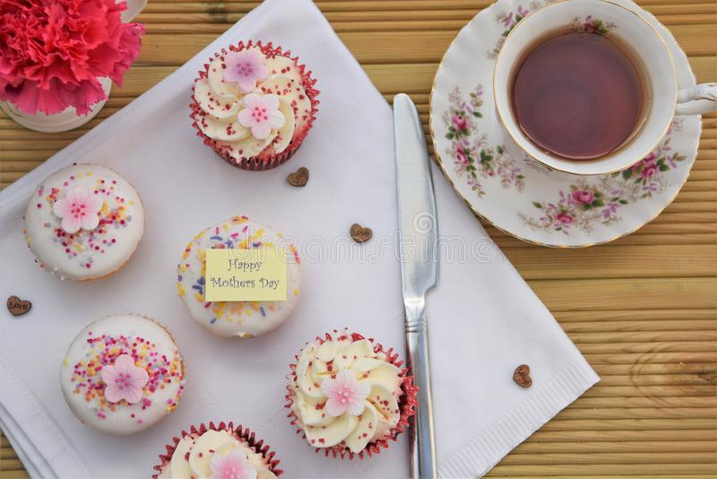 Happy mothers day cakes with iced pink flower decorations and cup of tea royalty free stock image