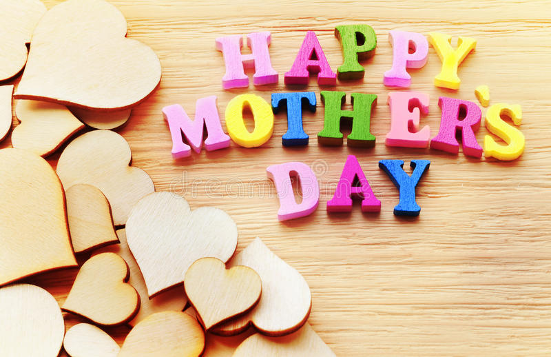 Happy Mothers Day colorful letters spelling greeting on wood table royalty free stock images