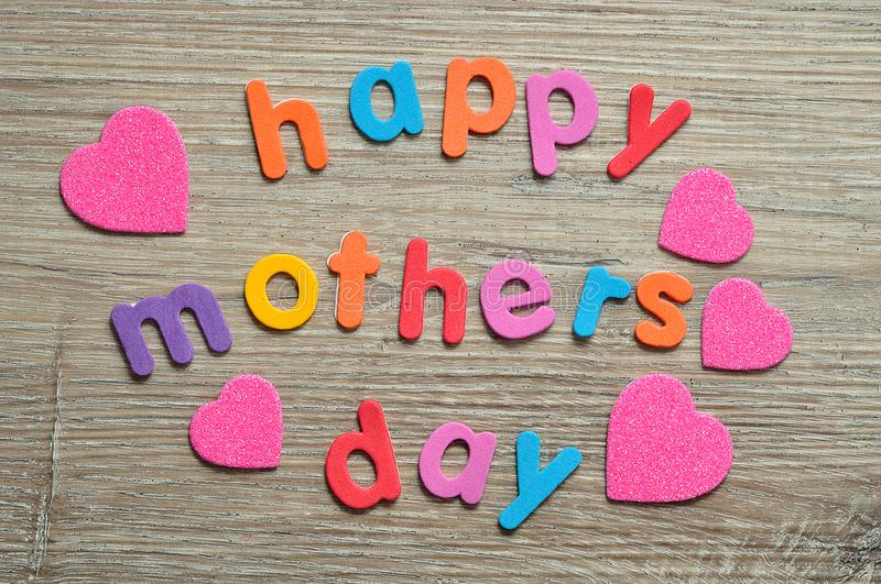 Happy mothers day in colorful letters with pink hearts stock photography
