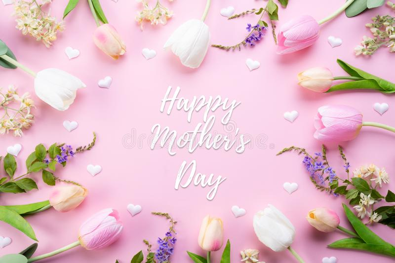 Happy mothers day concept. Top view of pink tulip flowers in frame with happy mother`s day text on pink pastel background. Flat stock photography