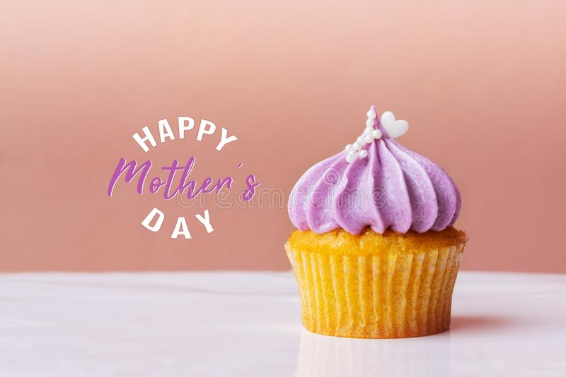 Happy Mothers Day, cute cupcake with small white heart on purple cream on pink background royalty free illustration