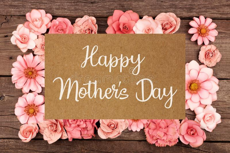 Happy Mothers Day greeting card with frame of pink paper flowers over wood. Happy Mothers Day greeting card with frame of rustic pink paper flowers over a dark stock image