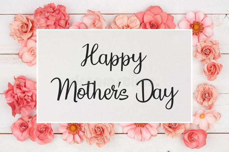 Happy Mothers Day greeting card with frame of pink paper flowers over white wood stock photos