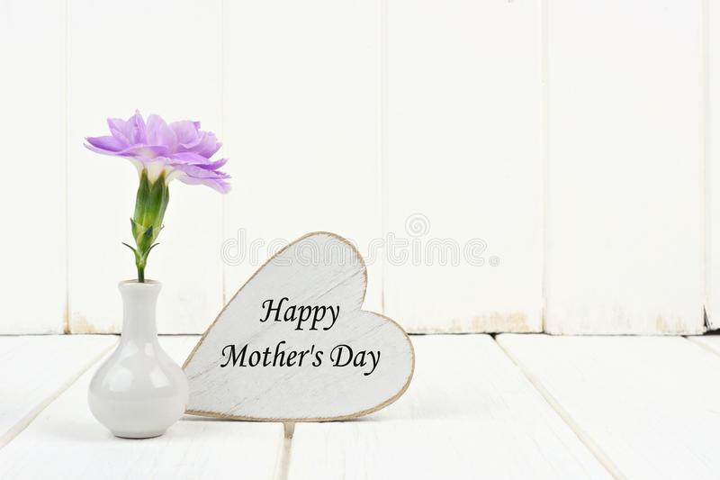 Happy Mothers Day heart tag with carnation against white wood. Happy Mothers Day tag with small vase and single purple carnation flower against a white stock photography