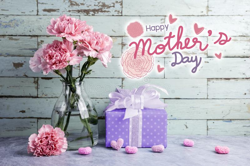 Happy mothers day message on wood background and pink carnation stock images
