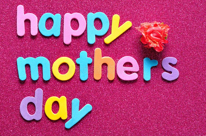Happy mothers day on a pink background with an artificial rose royalty free stock image