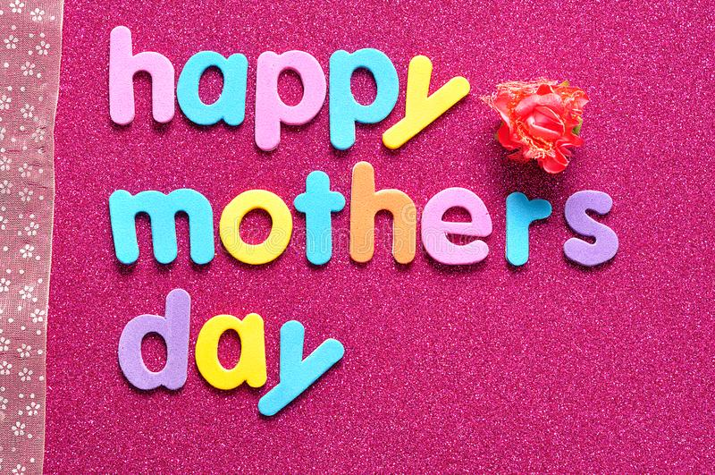 Happy mothers day on a pink background with a pink ribbon and an artificial rose royalty free stock images