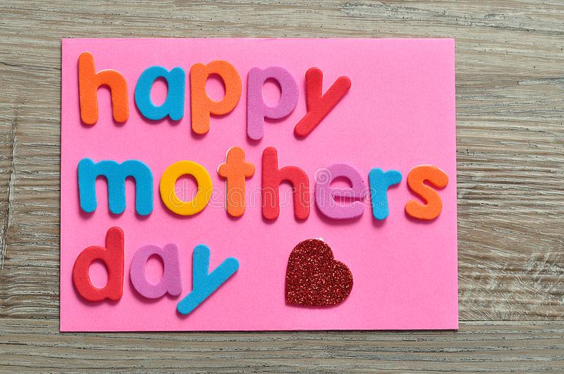 Happy mothers day on a pink note with a red heart royalty free stock photography