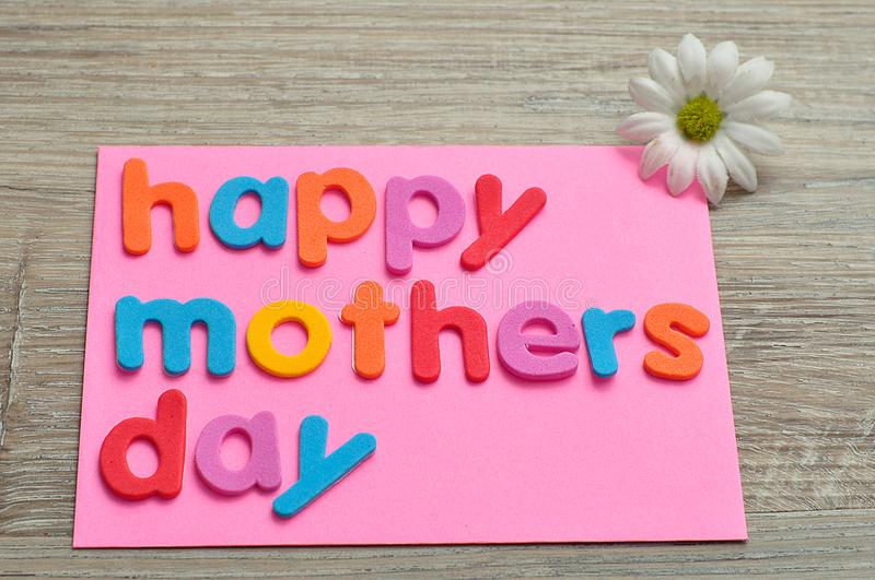 Happy mothers day on a pink note with a white daisy royalty free stock image