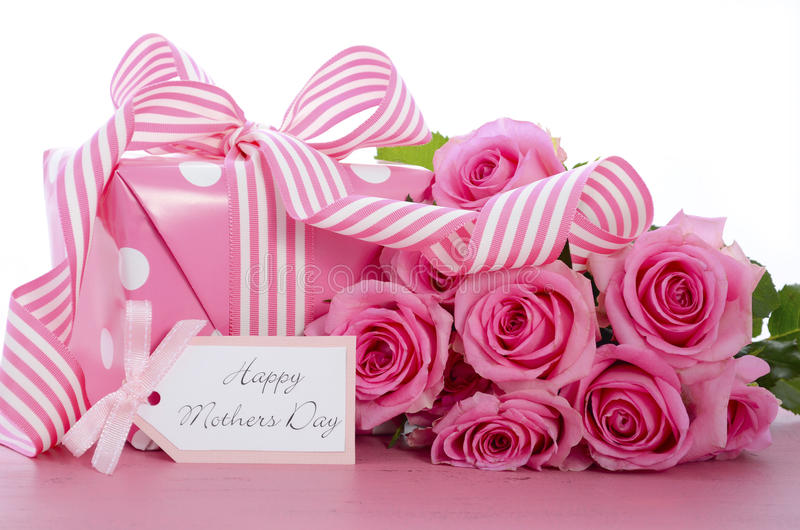 Happy Mothers Day pink polka dot gift. Happy Mothers Day pink polka dot gift with pink and white stripe ribbon and gift tag on vintage pink wood table royalty free stock images