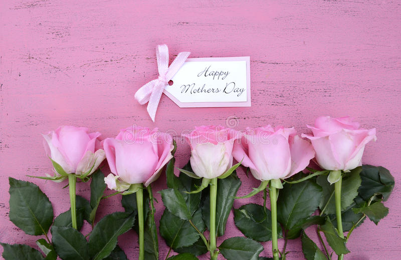Happy Mothers Day Pink Roses and Tea. Happy Mothers Day Pink Roses on Vintage style distressed pink wood table with gift tag royalty free stock photography