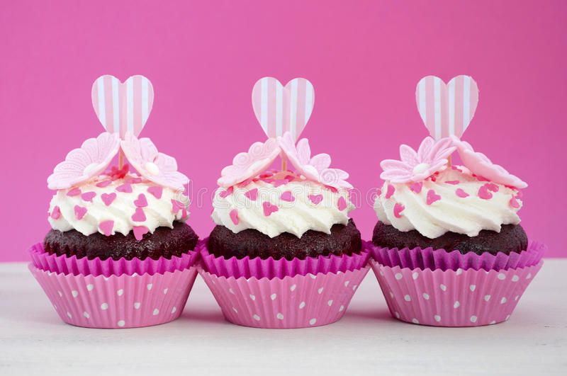 Happy Mothers Day pink and white cupcakes. Happy Mothers Day pink and white cupcakes with heart shape topper and hearts and flowers decorations on vintage white royalty free stock photos
