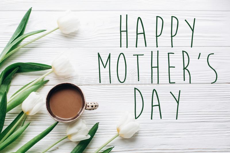Happy mothers day text sign on tulips and coffee on white wooden royalty free stock photography