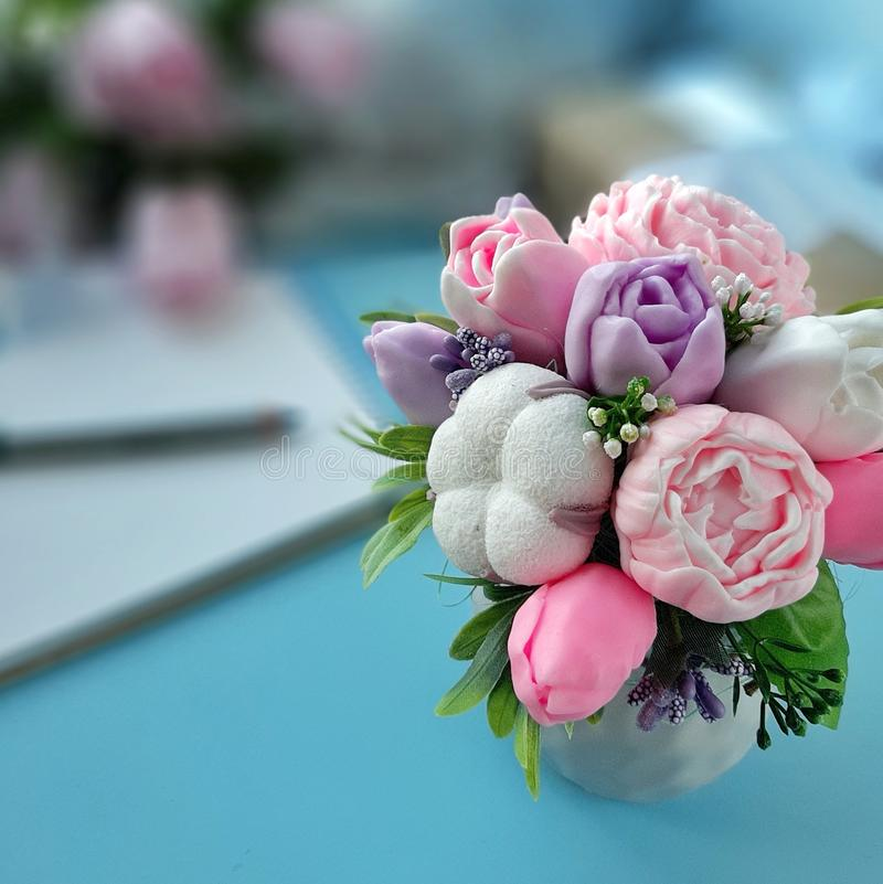 Bouquet of soap flowers on blue blurred background royalty free stock photography