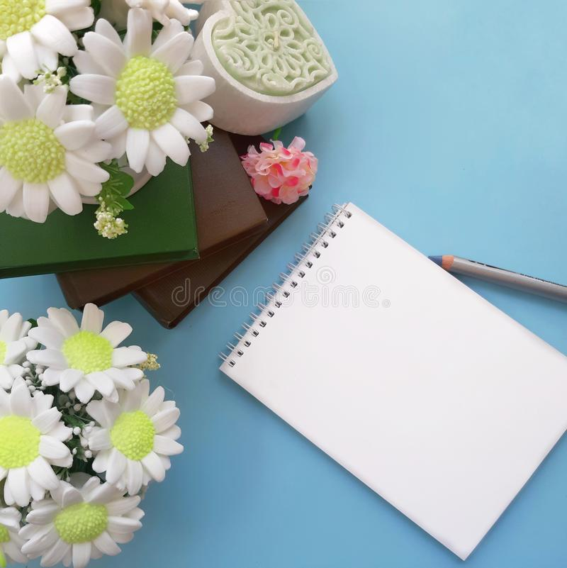 Bouquets of soap flowers, blank notepad with pencil, books on light blue background. Happy Mothers day, Womens day, Valentines day, Birthday or wedding greeting royalty free stock image