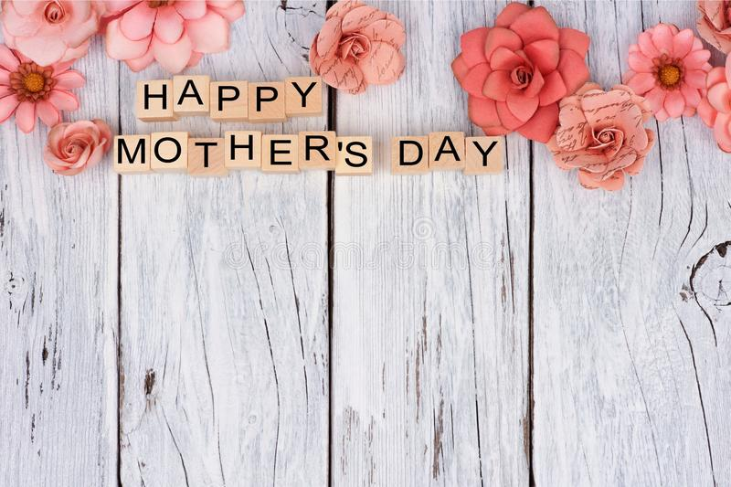 Happy Mothers Day wooden blocks with flower top border on white wood royalty free stock images