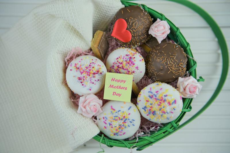 Happy mothers day words on a note in a basket of homemade cakes and fresh flowers royalty free stock image
