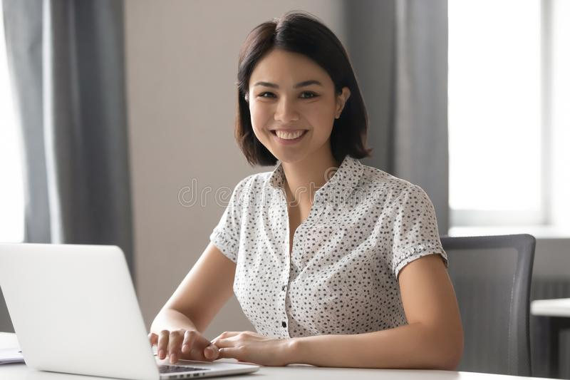 Happy motivated asian female employee working with computer portrait. stock photography