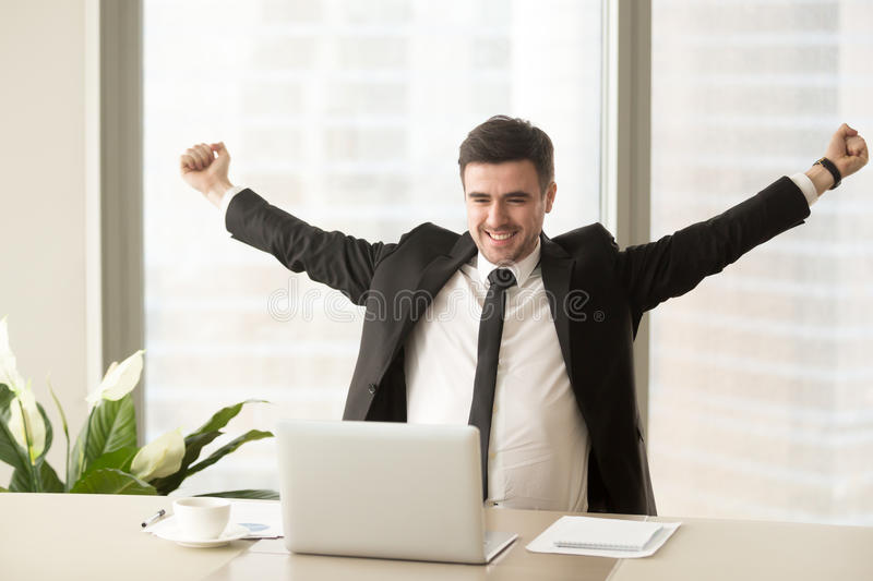 Happy motivated businessman in suit raising hands looking at lap. Happy businessman in suit raising hands looking at laptop, celebrating victory, stock trading royalty free stock images