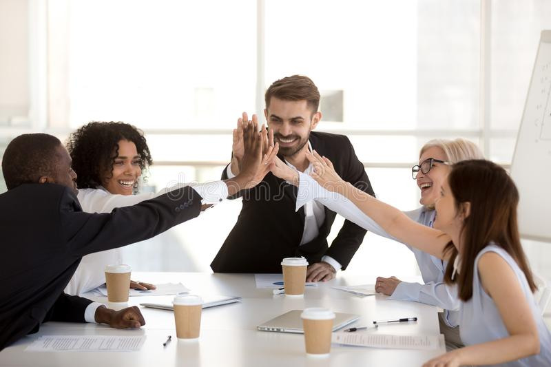 Happy motivated diverse business team people giving high five. Together celebrating goal achievement, team spirit, coaching engaging in corporate success, unity royalty free stock images