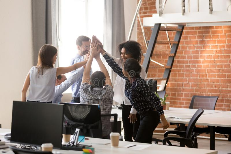 Happy motivated diverse office team giving high five together. Excited multi-ethnic employees group celebrating reward, startup success, good teamwork result stock images