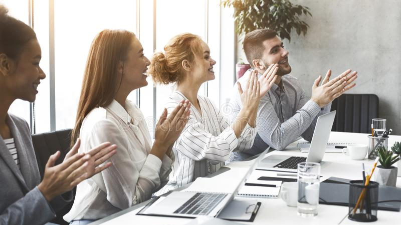 Happy motiveted business team applauding at conference stock photo