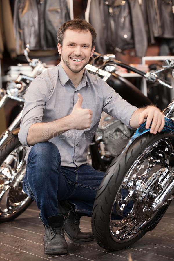 Happy motorcycle owner. Cheerful young men crouching near his ne. Happy motorcycle owner. Cheerful young man crouching near his new motorcycle stock photo