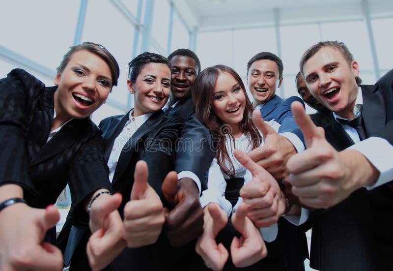 Happy multi-ethnic business team with thumbs up in the office. stock photo