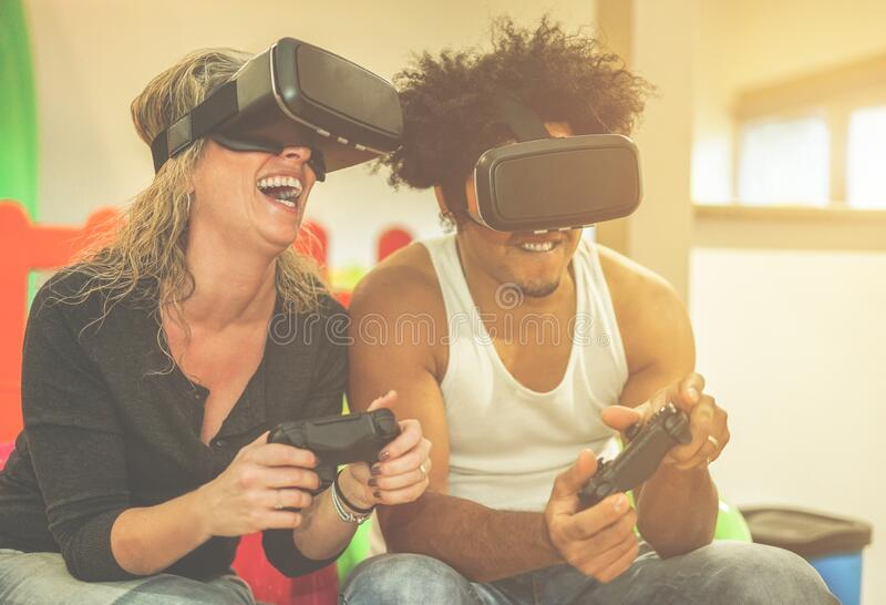 Happy multi ethnic couple playing video games virtual reality glasses in playground center - Cheerful people having fun with vr stock photography