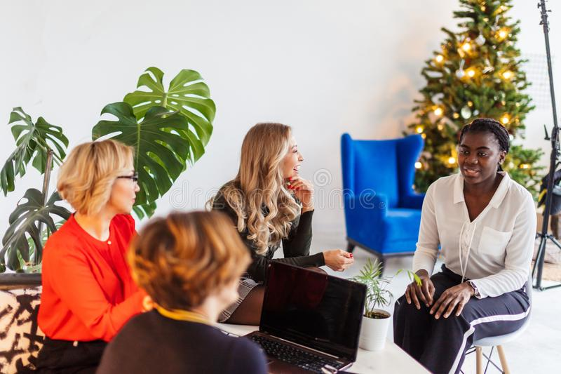 Happy multi-ethnic female friends meeting at hall after corporate training stock images