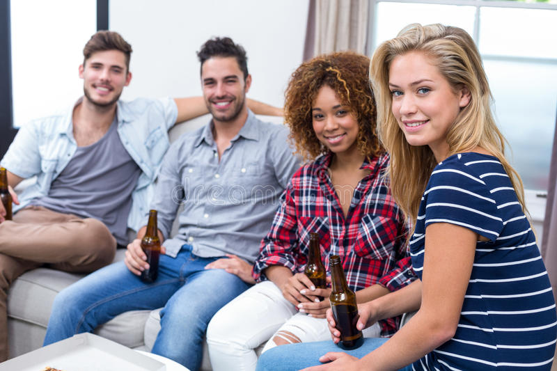 Happy multi-ethnic friends holding beer while sitting on sofa. Portrait of happy multi-ethnic friends holding beer while sitting on sofa at home stock photography