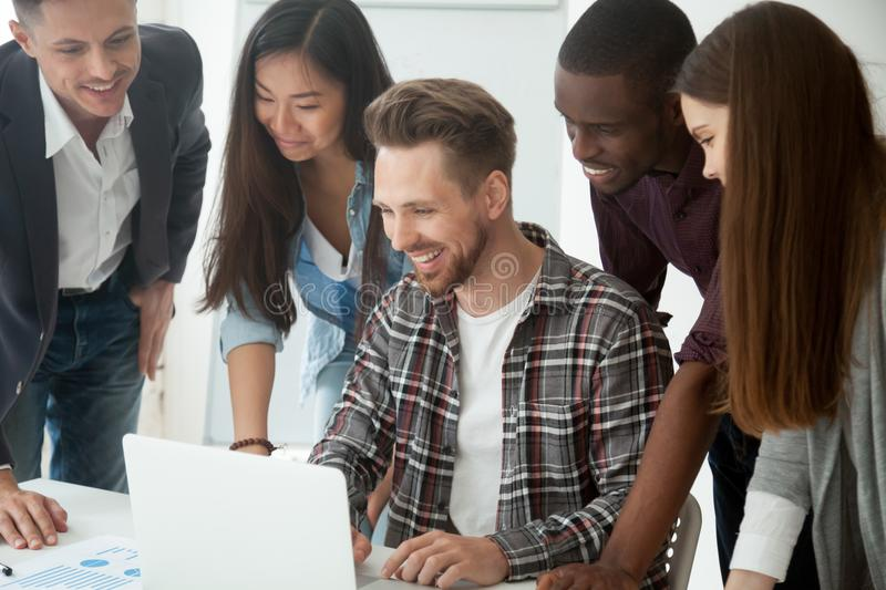 Happy multi-ethnic team excited by online result looking at lapt royalty free stock photos