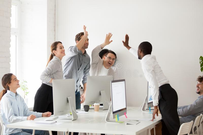 Happy multi-ethnic team giving high five together celebrating co. Happy multi-ethnic employees sales team giving high five together celebrating corporate success royalty free stock images