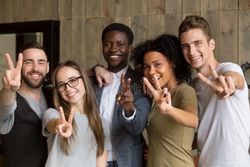 Happy multi-ethnic young people showing peace sign looking at ca royalty free stock photography