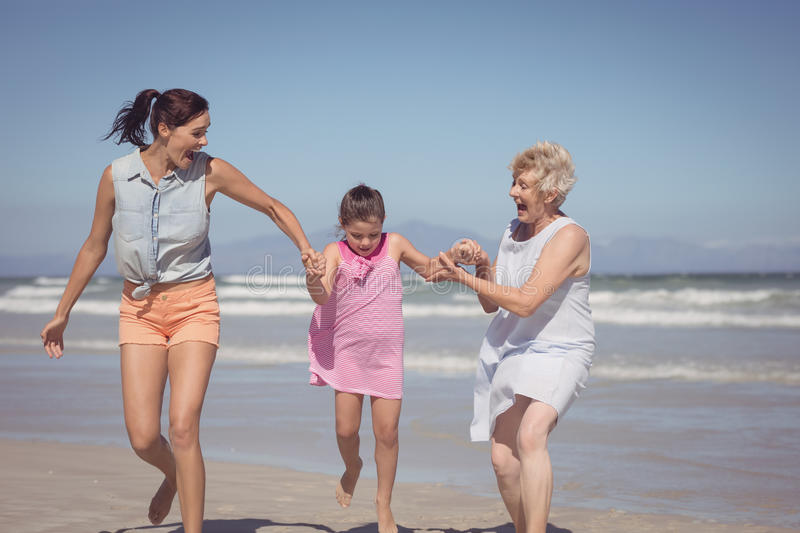 Happy multi-generation family playing at beach stock photo